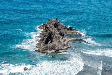 black rock in ocean waves near beach , aerial