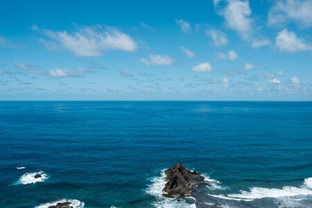 Ocean horizon with blue sky and rocks near beach  coast