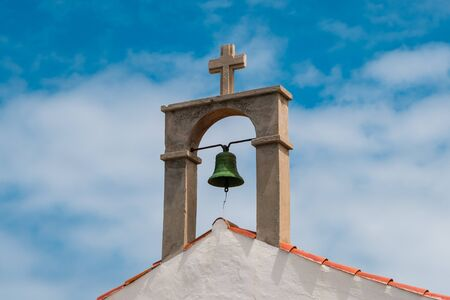 church bell and cross on rural church roof