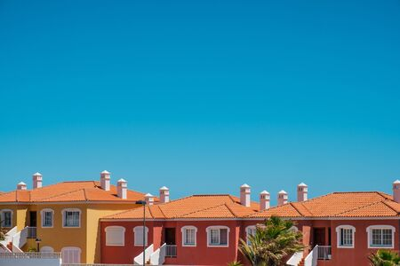 colorful apartment houses with blue sky copy space - real estate exterior