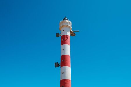 red,white lighthouse tower isolated on blue sky