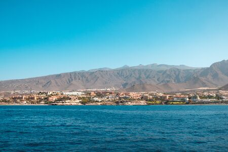 city and hotels at coast with mountain landscape background - ocean view on Tenerife Island