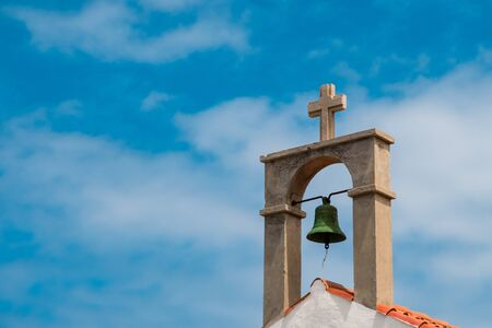 church bell and cross on church roof  -