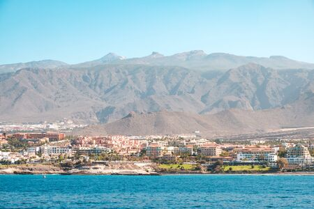 city with hotel buildings at coast with mountain landscape background - ocean view on Tenerife Island