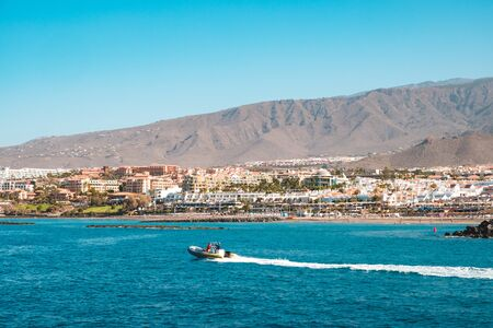 motor boat at ocean coast with beach and hotel in background, Tenerife 写真素材
