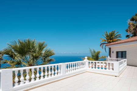villa with ocean view terrace, blue sky and palm tree background  -