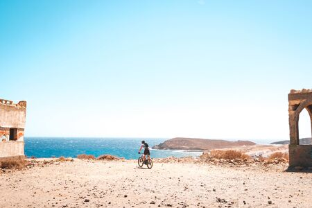 person on mountain bike bicycle in desert landscape near coast with ocean background
