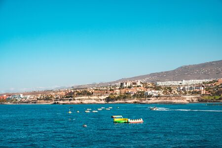 group of jet ski in ocean with hotels at coast in background