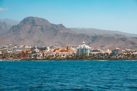 Ocean front hotels at coast view from boat on shore with mountain background 写真素材