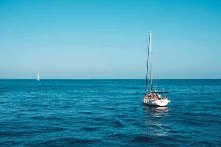 sailing boat with group of people on calm ocean on sunny day with clear blue sky