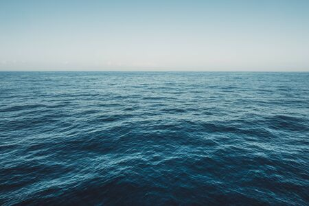 Calm sea surface with waves at sunny day - ocean background
