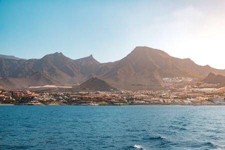 ocean view on shore with hotels and city and scenic mountain background - Coast of Tenerife - 写真素材