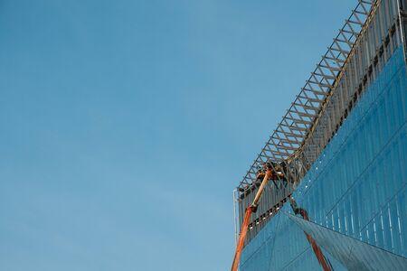 cranes on glass facade office building under construction