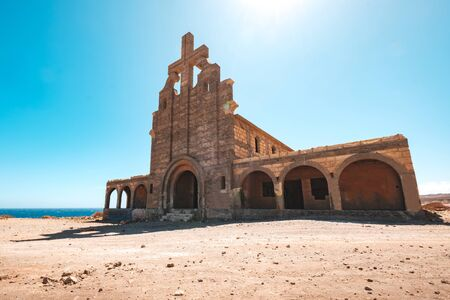 exterior of old church building ruin in sunny desert landscape -
