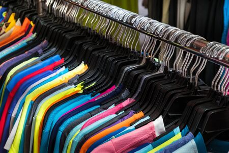 colorful t-shirts hanging on second hand clothing market