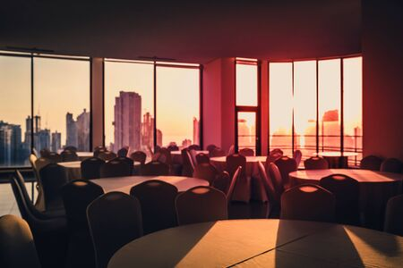 abstract blurry image of empty dining room with city  skyline and  sunset sky background -