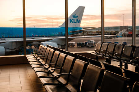 Amsterdam, Netherland - December, 2019: Empty seats in airport with KLM Airline airplane in background
