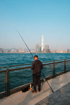 有钓鱼竿的Fisher人在海岸与香港的天际线,九龙