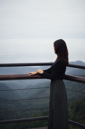 Young asian (Vietnamese) woman standing on balcony overlooking distant mountains in Tam Dao, northern Vietnam Stock Photo