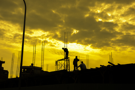 heavy risk: HDR effect of silhouette workers working at building construction side at sunset time