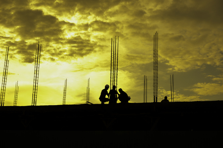 side effect: HDR effect of silhouette workers working at building construction side at sunset time