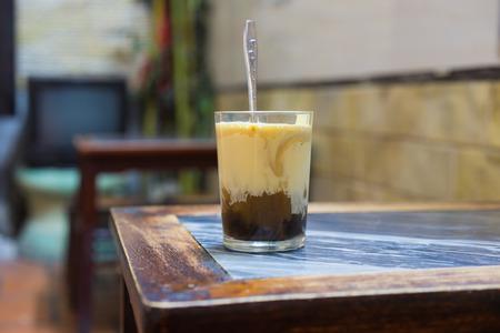 1946 년에 발견 된 하노이 (Hanoi)에있는 Giang 달걀 커피 한 잔. 커피는 잘게 자른 노른자와 다른 성분의 혼합물을 추가하기 전에 필터가 달린 작은 컵에 담겨져 있습니다. 스톡 콘텐츠 - 70588653