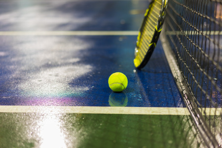 Tennis ball, racquet and net on wet ground after raining Imagens