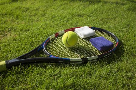 wristbands: Tennis ball, racket and wristbands on grass field ground under sunlight Stock Photo