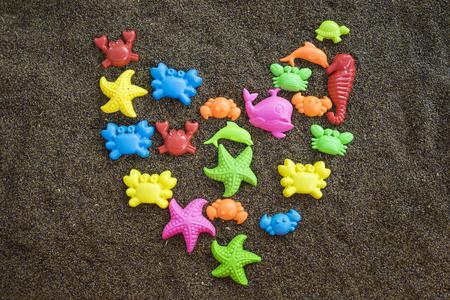 pink dolphin: Plastic sea animals on man made sand. Children toys