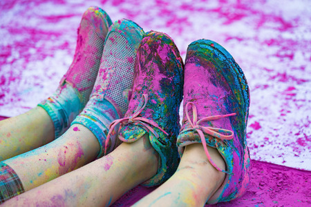 purple shoes: The colorful shoes and legs of teenagers with purple color powder in the public event The Color Run