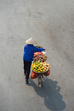 loaded: Aerial view of Asian vendor with tropical fruit loaded basket on bike Stock Photo