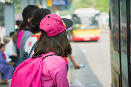 Asian girl waiting for bus at station Stock Photo