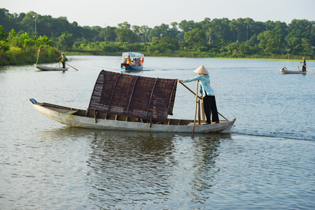 ship bow: Vietnamese woman rowing wooden boat on river