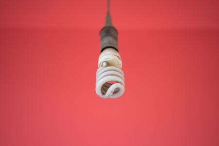 Energy saving light bulb against red wall background Stock Photo