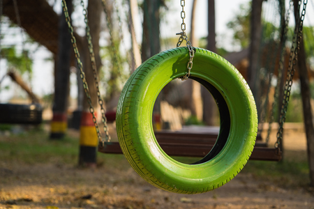 Color old car tire hanging on tree at playground