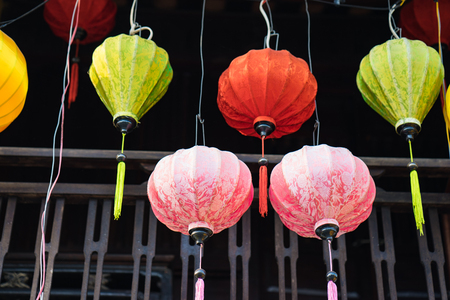 Colorful silk lantern hanging in front of vintage wooden house