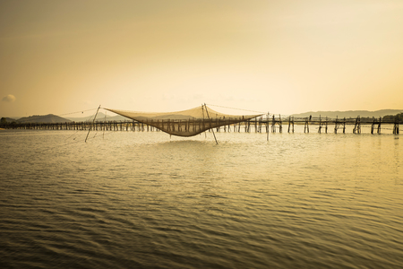 s trap: Panorama view of Ong Cop bridge ( Mr Tiger s wooden bridge) with big fish net trap by twilight period, the longest wooden bridge in Vietnam Stock Photo