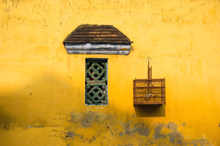 Aged yellow wall with small window and bird cage Stock Photo