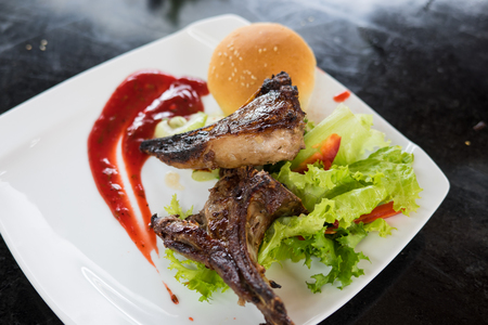 Grilled steak of lamb meat cut on slice with round bread, salad, oil, sauce and cup of orange juice