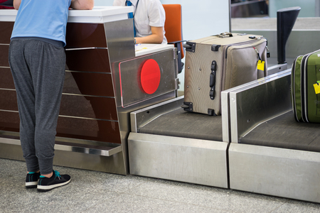 アジアの空港のチェックイン デスクで荷物の重み付け