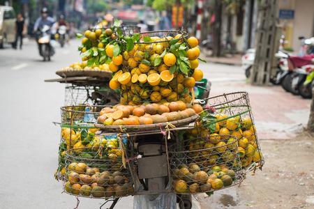 Full basket of orange fruit on vendor bike on Hanoi street, Vietnam Stock Photo