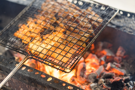 Barbecue meat cooking on fire - the ingredient of bun cha the famous Vietnamese noodle soup with bbq meat, spring roll, vermicelli and fresh vegetable served on bamboo flat basket