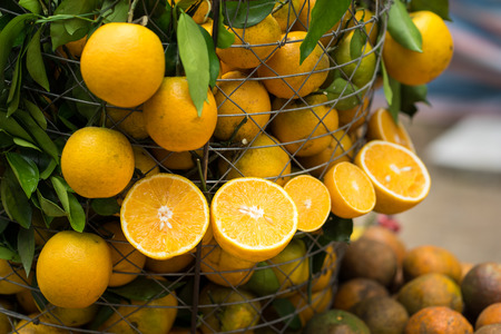 Tropical oranges hanging out and in basket. Focus on half cut orange Stock Photo