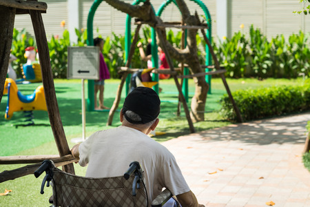 paraplegico: Old man sits on wheelchair looking at children playing on playground. Concept of youth recall, taking care of children. Foto de archivo