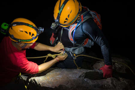 dark cave: Explorers help each others to tighten climbing equipments with rope, hook, belt in dark cave in Son Dong, the largest cave in the world Stock Photo