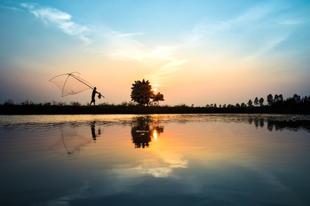 animal trap: Vietnamese rural countryside sunset scene with silhouette farmers carrying bamboo fish traps home