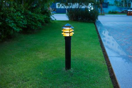 Illuminated outdoor light in apartment garden at twilight, evening. Stockfoto