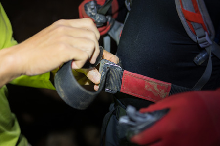 dark cave: Man hand tightening rock climbing equipments with rope, hook, belt in dark cave in Son Dong, the largest cave in the world