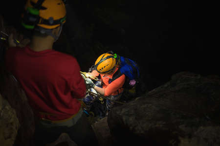 dark cave: People help each others to climb down of rock cliff in dark cave in Son Dong, the largest cave in the world in UNESCO World Heritage Site Phong Nha-Ke Bang National Park, Quang Binh province, Vietnam Stock Photo