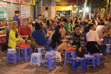 Hanoi, Vietnam - Nov 2, 2014: People drink beer on street at night in old quarter, center of Hanoi. Drinking beer on street is one of the most special culture of Hanoi. Redactioneel